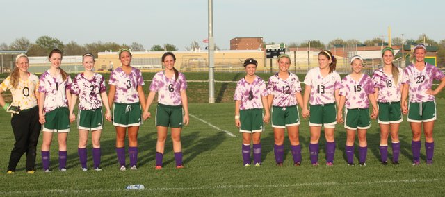 The Basehor-Linwood girls soccer team donned purple tie-dyed jerseys for Monday's game against Mill Valley. The Bobcats wore the jerseys to remember freshman Shealynn Hayes, who passed away last week. After the game, the starting lineup gathered, saving a spot for Hayes. Pictured, from left to right: Sophomore Brianne Kennedy, freshman Courtney Robinson, junior Hailey Robinson, freshman Nicole Rutherford, sophomore Megan Sixta, senior Jordan Nirschl, junior Ally Laney, sophomore Raeney Seaton, sophomore Julie Lough and senior Kara Stephens.