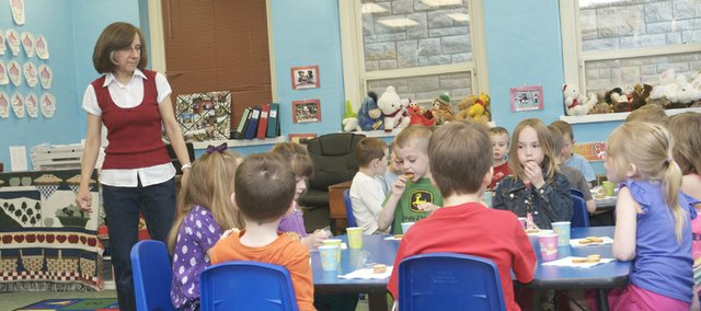 Rainbow Experience Preschool lead teacher Sue Demarest watches as children in the preschool's kindergarten readiness class enjoy a snack. The preschool in marking its 50th anniversary in the community this year.