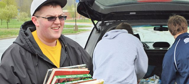 Graham Cannon, a Boy Scout with Troop 93, carries books donated during a drive-thru book drive Saturday morning at Mill Valley High School. Graham organized the drive to fulfill the community service project requirement for becoming an Eagle Scout.