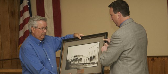 City Administrator Chris Lowe presents Ken Wagner a framed photograph of downtown Baldwin City circa 1900 at Monday's city council meeting soon before Marilyn Pearse was sworn in as mayor. Wagner four-year term as mayor of Baldwin City ended with the conclusion of old business on the agenda at the meeting.