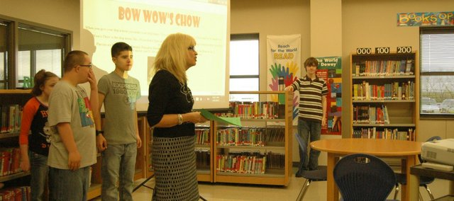 Students from Tonganoxie Middle School spoke Thursday during the Tonganoxie Chamber of Commerce breakfast at the TMS library. Students in special education classes told chamber members about their BowWow Chow dog treats that they make during class and then sell. Pictured, from left, are Tesla Felty, Seth Reynolds, Angel Lucerno and teacher Nancy Overacker. At far right is Blake Williams, a TMS student in the gifted program who helped design a website for the group.