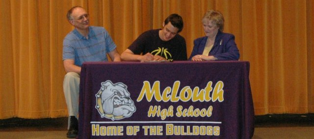 McLouth High senior Carter Gish, center, has signed a national letter of intent to play basketball at the University of Saint Mary.