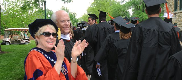 Baker University President Pat Long applauds the Class of 2013 as it files by on its way Sunday to the Collins Center for commencement.