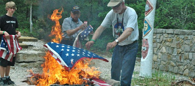 Pat Donahue, right, leader for Troop 61, adds another flag to the fire during the retirement ceremony, while VFW member Pete Gomez (center) and Scout Kardal Hart look on.