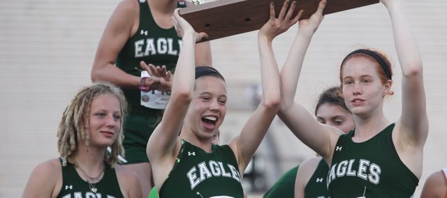 Maranatha Christian Academy's Caroline Bingham (1404) and Katherine Smith lift the team's Class 2A state track and field championship trophy Saturday in Wichita.