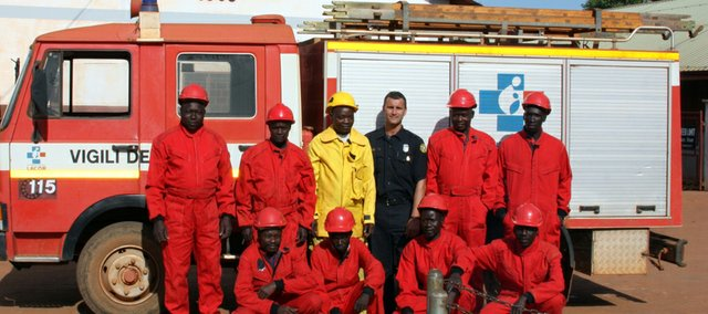 Ryan Beasley, standing third from right, poses with local firefighters in Uganda on a recent trip for the Medical Missions Foundation.