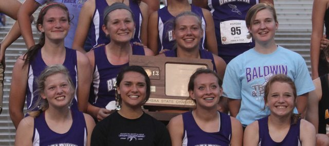 Members of the Baldwin High School girls track team pose with the trophy they won for finishing first Saturday at the 4A state track and field championships at Wichita. It was the school's third state title in four years.