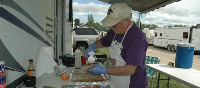 Jim Belt of Linwood, member of the barbecue team Mad Hogs and an Englshman, prepares chicken at the McLouth BBQ Blowout on Saturday in McLouth's Prairie Park.