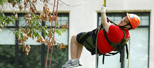 Devan Glenny, a college senior from Lebanon Valley College in Annville, Pa., leaves his wheelchair on the ground as he ascends into a tree Thursday on the Baker University campus. Eight research interns were selected from across the country to participate in a 10-week, canopy-research project funded by the National Science Foundation. The interns will be climbing the trees at various heights to collect moss and lichen samples for measuring the density and diversity of microscopic animals called tardigrades. Glenny, who is interested in pursuing a career that involves field research, says he was drawn to the project when he found out it was open to students with wheelchairs.