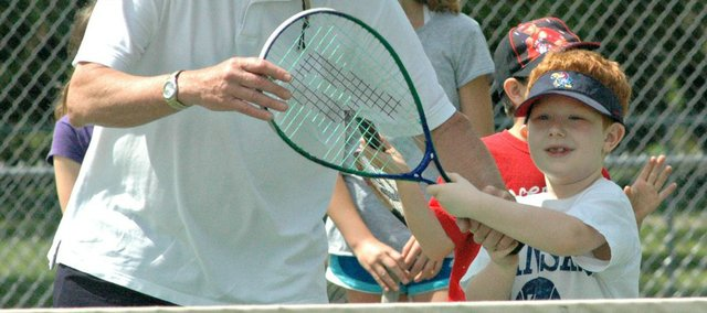 Tyler Stanwix, right, gets instruction from Sid Kanter during a youth tennis camp last week at Chieftain Park.