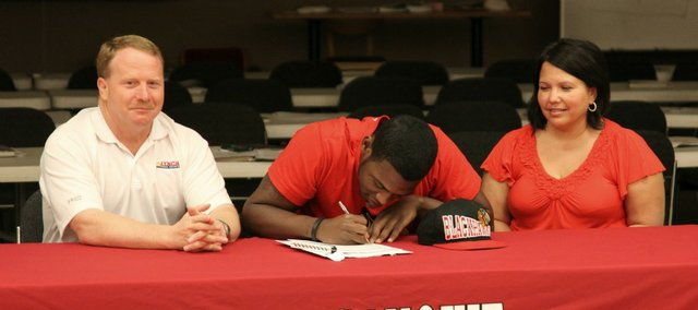 Tonganoxie High graduate Julius Coats, center, has signed a letter of intent to wrestle at Pratt Community College.