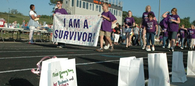 Survivors begin the traditional first lap at the 2012 Relay For Life of Kaw Valley, which includes participants from Edwardsville, Bonner Springs and Basehor. This year's event will begin at 7 p.m. Friday, June 14, at the track at Bonner Springs High School.