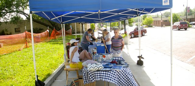 Lisa Jewell (left in white) talks to fellow vendor Linda Hoffman on Saturday morning at the Baldwin City Farmers' Market. The market is open from 8 to noon Saturdays in the 700 block of High Street.