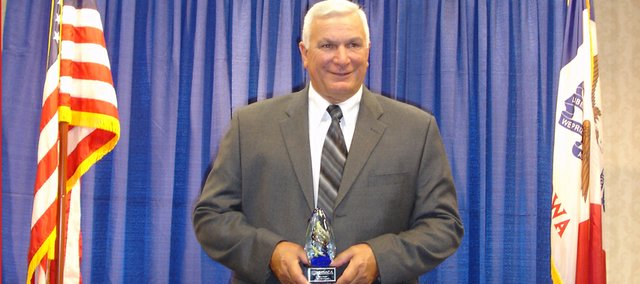 Baldwin High School girls track coach Ted Zuzzio holds the trophy he received when he was inducted into the National High School Athletic Coaches Association Hall of Fame for his accomplishments as girls basketball and track coach during his 37-year career at BHS.