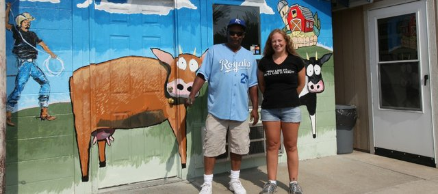 Teri Holloway, left, and Kristin Conley, right, stand near one of two murals at Grandpa's Burger Box, which Conley owns. Holloway painted the murals for Conley, who envisioned the scene during a dream.