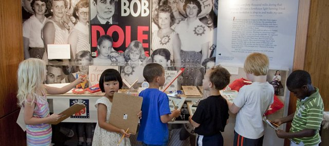 Children from the Boys and Girls Club work on a scavenger hunt at the Dole Institute of Politics at Kansas University on Monday. The institute was celebrating Bob Dole's 90th birthday with cake and kid-friendly activities.