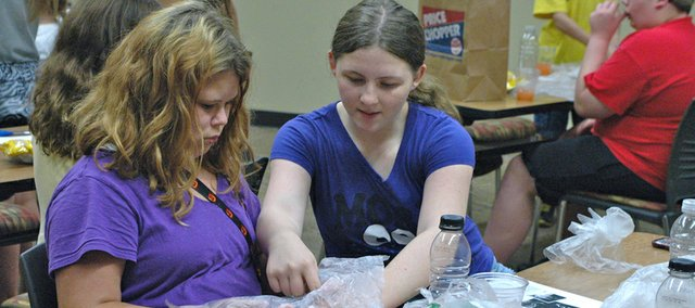 Kaspien Stogner, left, gets some help creating her jellyfish from Teighlor Davis at Monday's Teenopolis program at the Bonner Springs City Library. The library continues to see an increase in overall visits and use, as well as participation in its summer reading program.