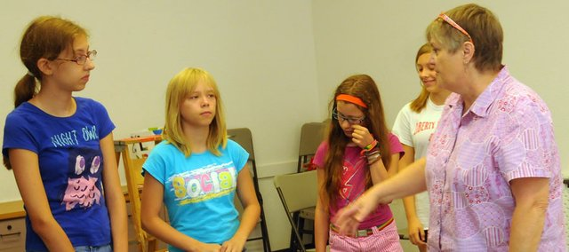 "Jennifer Glenn, right, gives stage tips to (from left) Ella Mozier, Tena Hicks and Ella Conover during a rehearsal Monday for ""Alice in Wonderland."" Glenn is the instructor in a two-week theater camp at the Lumberyard Arts Center."