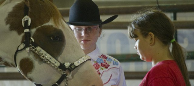 Journal-World Photo.Hannah Spriggs, 14, left, holds her horse Sophie, while her cousin Sophie Dechant, 11, rubs the horses nose before showmanship competition Saturday, July 27 at the 4-H Horse Show at the Douglas County Fairgrounds. Both girls are members of the Vinland Valley 4-H club. The Open Horse Show is today and Monday the fairgrounds open for entries in several 4-H and Open classes including food and arts and crafts.