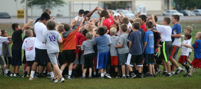 Youth football campers huddle before the start of Thursday's session at the THS practice field. This year's camp drew 110 players.