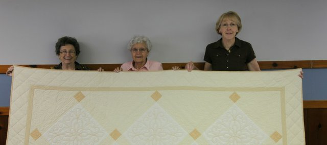 "Alice Schneider, Mary Alice Hund and Brenda Hruska stand with the St. Joseph Quilters entry in the Leavenworth County Fair. The quilt is called ""Serenity."" The Leavenworth group earned a blue ribbon and a red ribbon for their work."