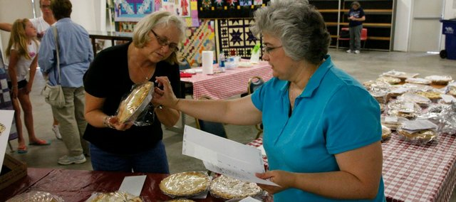 Crystal Miles and Patty Schalinger organize pies for the inaugural Leavenworth County Fair Pie Baking Contest. The Leavenworth County 4-H Foundation put on the event, which raised nearly $600 for the foundation.