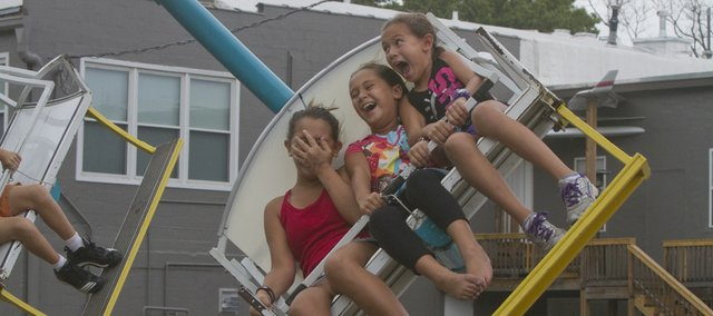 Sisters (from left) Laureen Shumate 12, Lacey Shumate 7, and Logan Shumate, 9, all of Bonner Springs, rode the Cobra during Tiblow Days 2012 in Bonner Springs.