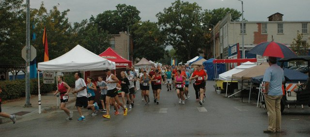 Tiblow Trot runners round the first corner at Second and Cedar streets in last year's event, as then-city councilman Jeff Harrington (far right) looks on.
