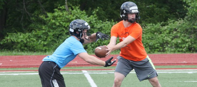 SMNW senior Jake Gilliam takes a hand-off from junior Clay Drouillard during the Cougars' June team camp. SMNW seeks to improve on 2012's 2-7 record.