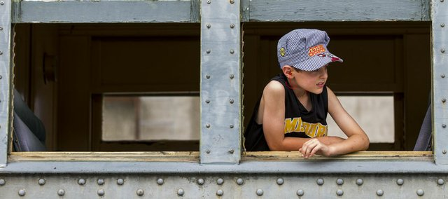 "Wearing a ""future engineer"" cap, seven-year-old Jack Barker, of Lee's Summit, Mo., looks out from a passenger car window while waiting to depart from the Midland Railway Depot in Baldwin City during the annual Railfest event Saturday.