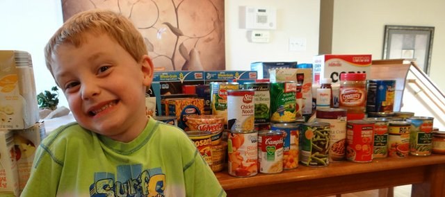 Jack Best, 5, smiles in front of the food he collected Aug. 24 by going door-to-door in his Fire Tree neighborhood. Jack and his mother Candi Best delivered the food Saturday to the Baldwin City Community Food Pantry.