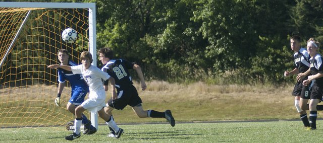 Baldwin junior Noah Pippert, in white, races to the ball in front of the Paola goal in the Bulldogs' 7-0 home-opening victory. The team had many scoring chances in the match played almost entirely on Baldwin's side of the field.