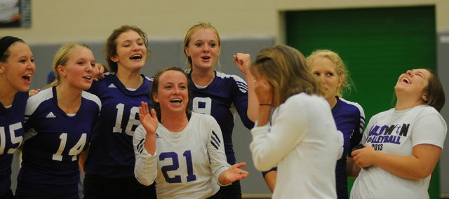 The Baldwin volleyball team members urge coach Jill Brown (in white) to celebrate with a dance shortly after defeating Paola to win Saturday's Frontier League Tournament title in De Soto. The Bulldogs didn't lose a set in its five victories at the event.