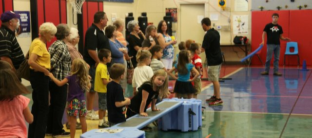 Tonganoxie Elementary School students listen to physical education teacher Jeremy Goebel alongside their grandchildren Friday during Grandparents Day activities.
