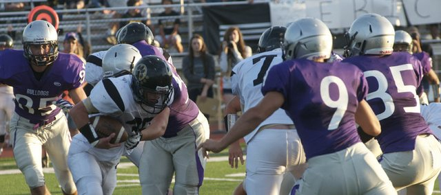 The Baldwin defensive line swallows up a Paola runner early in the Bulldogs' 28-9 victory Friday against the visiting Panthers. The defensive was strong all night, giving up only three first downs through the first three quarters and one sustained Panther drive in the game.