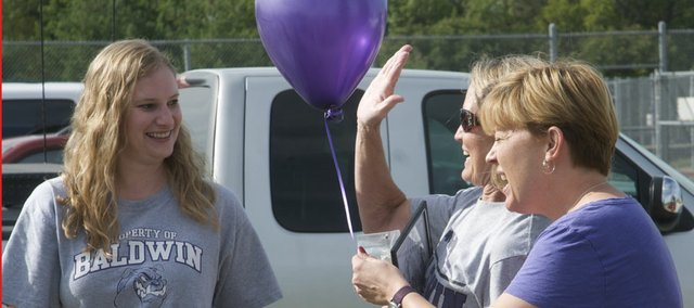 Katie Marten, left, smiles as Susie Martin calls for a high five after the two Baldwin High School teachers learned Kathy Gerstner, with baloon, that their application for a Baldwin Education Foundation innovative project grant had been accepted for funding. The grant provided money for the purchase of recycling bins at the school.