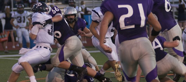 Baldwin senior Colton Stark, 66, wraps up St. James quarterback Alex King for no gain in the second quarter of Bulldogs' 56-18 victory Friday against the Thunder.