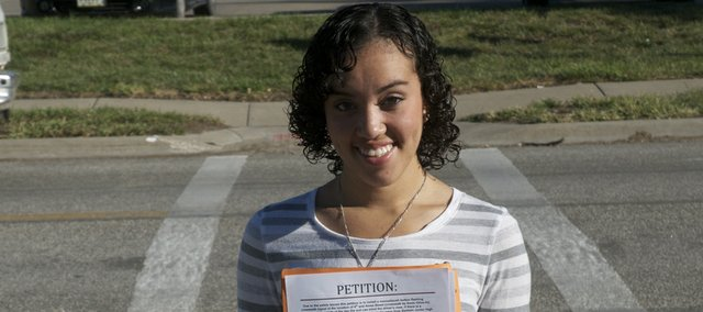 Shai Jackson is going door-to-door in Baldwin City with a petition asking for support for a crossing light at the crosswalk at U.S. Highway 56 and Fourth Street. Jackson received a ticket at the crosswalk because she couldn't see a pedestrian waiting to cross the highway when she was blinded by the sun.