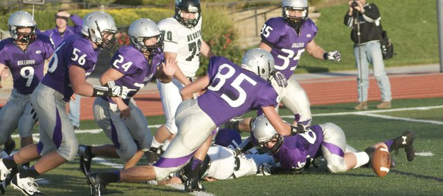 Baldwin's Luke Fursman pounces on a fumble inside De Soto's 10-yard line in the first quarter of the Bulldogs' 49-7 victory Saturday against the Wildcats. The fumble recovery set up Baldwin's first touchdown.