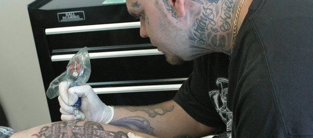 Donnie McQuitty, owner, begins white highlights on a tattoo for a client who wanted to commemorate the death of his grandmother Tuesday at Righteous Tattoo Studio. The faith-based tattoo studio is the first to ever locate in Bonner Springs.
