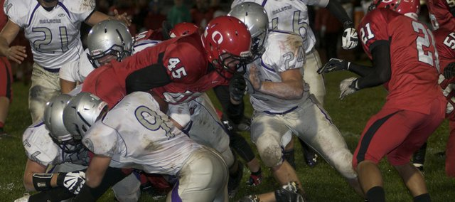 Joel Katzer, 9, his twin brother Jake, 24, Quinn Twombly, 56, and another Bulldog team to stop Ottawa's Kord Ferguson in the first half the the Bulldogs' 61-0 victory Friday against the Cyclones. The defense earned the team's first shutout of the year in the game.