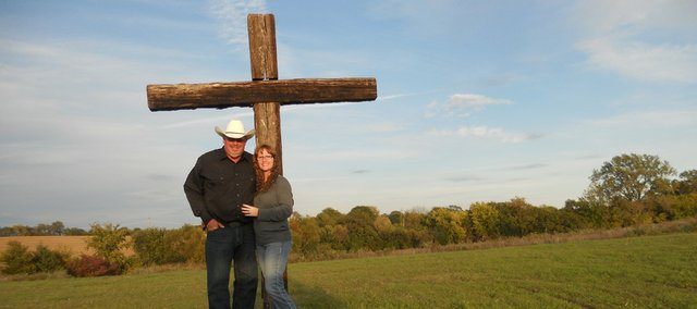 Mark and Joycelyn Yates pose with their dog, Ruger, near a cross built on the Freedom Farm ministry in rural Bonner Springs.