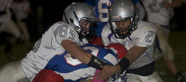 Seniors Luke Fursman (left) and Cornell Brown stop a Santa Fe Trail runner for a loss in Baldwin's 49-7 victory Friday. The Bulldogs will play for an outright Frontier League championship and an undefeated season Thursday against Eudora.