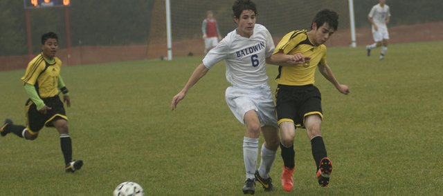 Baldwin's Joel Dixon, left, battles a Coffeyville player for the ball in the second half of the Bulldogs' 8-0 victory Tuesday in 1A-4A regional soccer play. With the win, Baldwin will play Ottawa today at home for the right to advance to the state tournament.