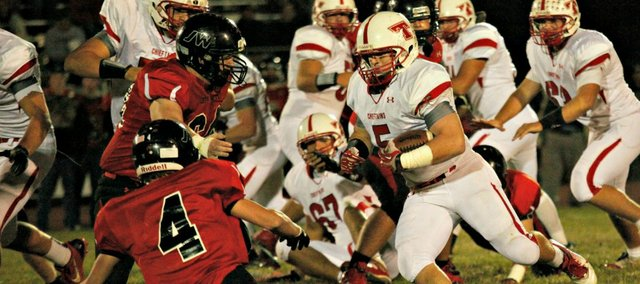 Shane Levy takes on a pair of Jeff West defenders. Levy ran for 79 yards and a touchdown on offense and had two interceptions on defense in Tonganoxie's 34-33 win.