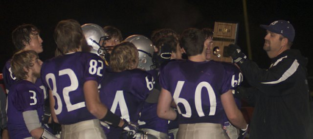 The Baldwin Bulldog seniors accept the first-place district plaque Thursday from BHS activities director Gary Stevanus after defeating rival Eudora to complete a perfect 9-0 season. With the win, the undisputed Frontier League Bulldogs will play St. James Academy Tuesday at home in the first round of the state 4A playoffs.