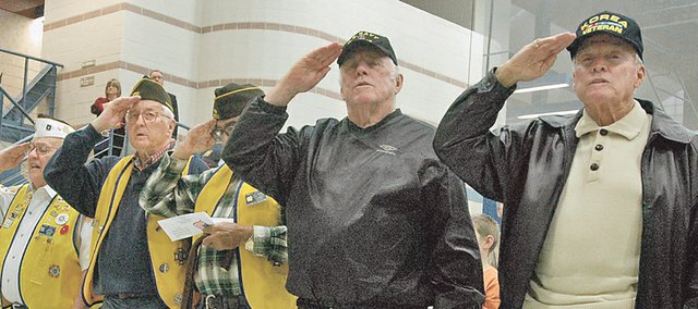 Veterans salute while the national anthem is sung by Mallory Keating at the City of Shawnee's 10th annual Veterans Day Celebration.