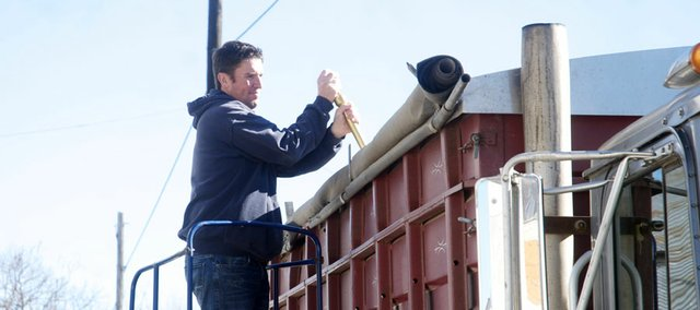 Baldwin Feed Company owner Steve Wilson collects a sample for testing from a load of soybeans delivered Monday to the elevator. Wilson said after a busy weekend at the elevator, the fall harvest is winding down.