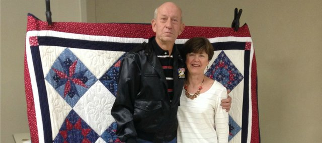 Pete Novosel, left, stands with his wife, Pat, in front of a Quilt of Valor that Tonganoxie VFW Post 9271 presented to him Wednesday, Nov. 20, at the VFW Post Home.