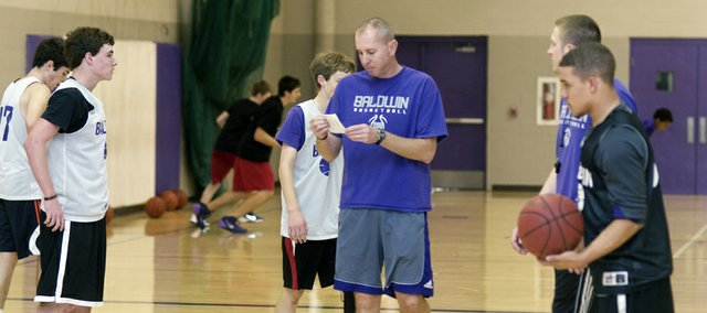Baldwin High School boys basketball coach checks his practice schedule Tuesday during the Bulldogs' workout. The senior-laden team opens Friday against Jeff County North.
